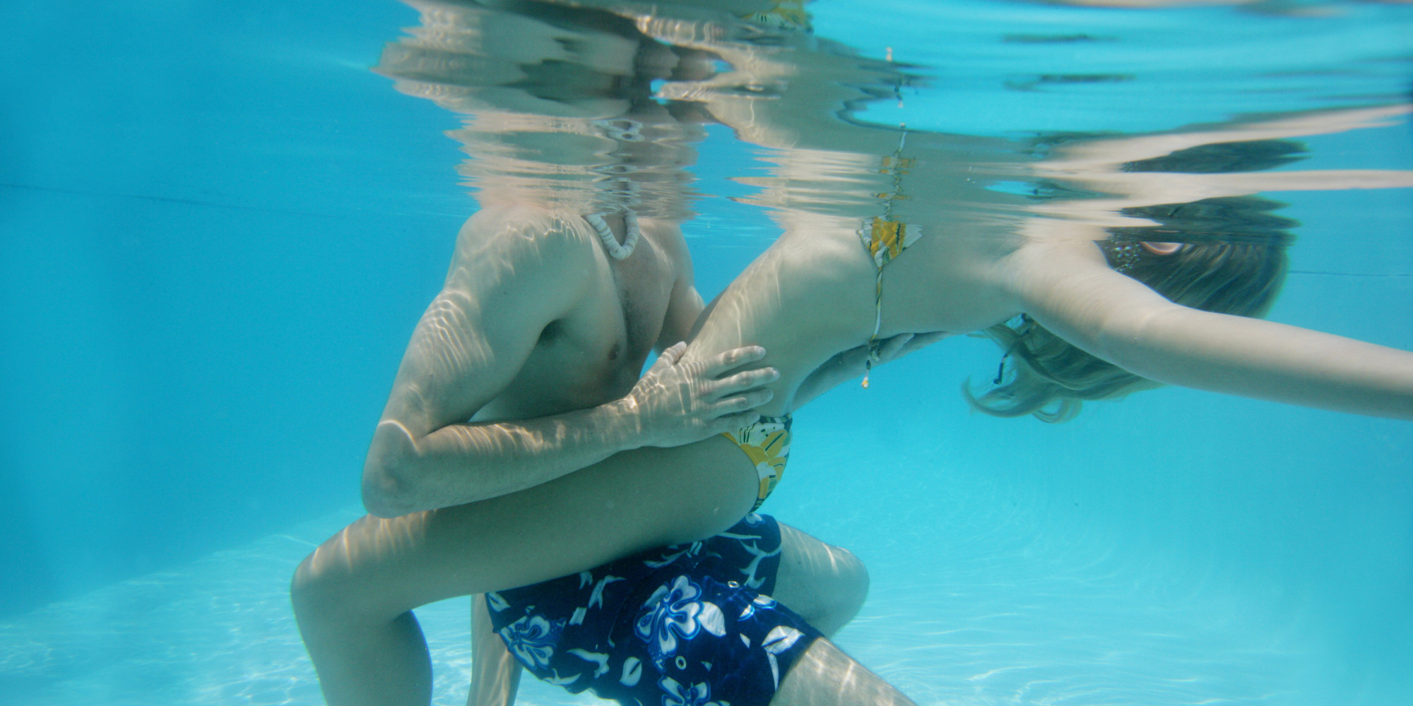 Cropped view of a couple holding each other in a pool